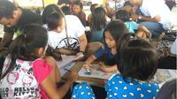 Setiap akhir pekan, sekelompok anak muda ini merelakan waktu mereka untuk mengajar anak-anak usia sekolah di Kompleks Pasar Bersehati Manado. (Liputan6.com/Yoseph Ikanubun)