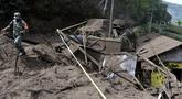 Seorang tentara berjalan melewati rumah-rumah yang rusak akibat tanah longsor yang dipicu gempa bumi di Bangli, di Bali, Sabtu (16/10/2021). Beberapa orang tewas dan lainnya luka-luka saat gempa berkekuatan sedang dan gempa susulan menghantam pulau itu Sabtu dini hari. (AP Photo/Dewa Raka)
