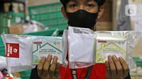 Pekerja menunjukkan paket obat COVID-19 di salah satu gerai ekspedisi SiCepat di Jalan K.S Tubun, Petamburan, Jakarta, Sabtu (17/7/2021). Pemerintah resmi membagikan 300 ribu paket obat gratis untuk pasien COVID-19 yang menjalani isolasi mandiri di Pulau Jawa dan Bali. (Liputan6.com/Herman Zakharia)