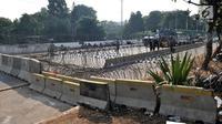 Pembatas beton dan kawat berduri menutup akses menuju Gedung DPR RI di Jalan Gatot Subroto, Jakarta, Kamis (26/9/2019). Pasca demonstrasi mahasiswa dan pelajar selama dua hari, Polisi menutup akses jalan mulai dari simpang Gerbang Pemuda. (merdeka.com/Iqbal S Nugoroho)