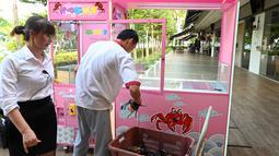 Pekerja restoran memasukkan kepiting ke dalam mesin capit di Singapura, 23 Oktober 2019. Pengunjung bisa mencoba menangkap kepiting hidup dari mesin capit itu dengan kupon seharga US$ 5 dan jika berhasil, restoran akan memasakkannya secara  gratis. (Roslan RAHMAN / AFP)