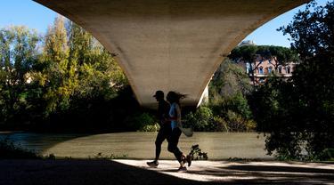 Orang-orang berlari di sepanjang sungai Tiber ketika pemerintah memberlakukan tindakan yang lebih ketat untuk mengekang penyebaran Covid-19 (novel coronavirus), di Roma tengah (17/11/2020). (AFP/Tiziana Fabi)
