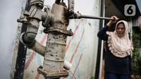 Warga menggunakan air tanah yang dipompa secara manual di kawasan Jakarta, Rabu (6/10/2021). Dirjen Cipta Karya Kemen PUPR Diana Kusumastuti mengimbau Pemprov DKI menyediakan air baku bagi masyarakat agar warga DKI Jakarta tidak lagi menggunakan air tanah. (Liputan6.com/Faizal Fanani)