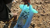 Seorang penambang mengumpulkan jarum suntik yang telah digunakan di Tambang batu giok di Hpakant, Myanmar, 29 November 2015. Kecanduan narkotika sudah merabak pada penambang batu giok. (REUTERS/Soe Zeya Tun)