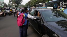 Petugas Dinas Perhubungan membagikan selebaran sosialisasi pemberlakuan sistem ganjil genap di pintu masuk Gardu Tol Cibubur 2, Jakarta, Senin (16/4). Aturan ini diujicobakan di Gerbang Tol pada  Senin 16 April 2018. (Liputan6.com/Faizal Fanani)