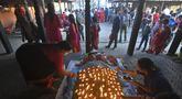 Seorang umat Hindu melakukan ritual dengan berbaring di tempat tidur yang ditutupi dengan 108 lampu minyak menyala pada hari kesepuluh festival Dashain di sebuah kuil di Bhaktapur di pinggiran Kathmandu (15/10/2021). (AFP/Prakash Matematika)