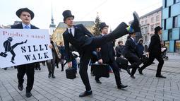 Seorang pria mengenakan kostum berjalan dengan mengangkat tinggi kakinya di Brno, Republik Ceko (7/1). Mereka mengenakan kostum tersebut untuk mengenang grup komedi asal Inggris, Monty Python. (AFP Photo/Radek Mica)