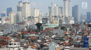 Lansekap pemukiman penduduk berlatar gedung bertingkat terlihat dari Tanah Abang, Jakarta, Selasa (21/5). Laporan Oxford Economics berjudul Global Cities 2018 menyebut Jakarta akan jadi kota dengan jumlah penduduk terbesar di dunia pada 2035, yakni 38 juta jiwa. (Liputan6.com/Immanuel Antonius)