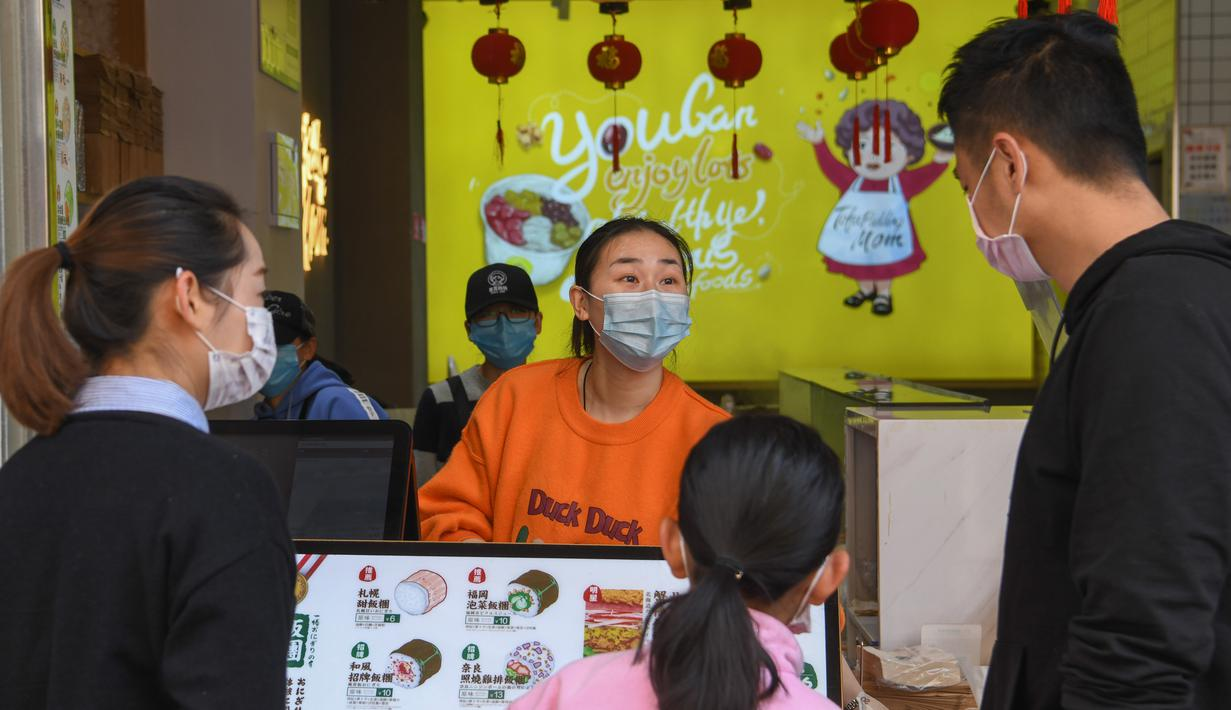 Pedagang melayani pembeli di toko makanan di Distrik Xiling, Kota Yichang, Provinsi Hubei, China, Jumat (20/3/2020). Aktivitas komersial warga Yichang berangsur normal menyusul meredanya kasus virus corona COVID-19 di China. (Xinhua/Cheng Min)