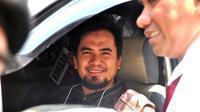Penyanyi dangdut yang tersangkut kasus pelecehan seksual Saipul Jamil tersenyum di mobil saat menjalani rekonstruksi. (Adrian Putra/Bintang.com)