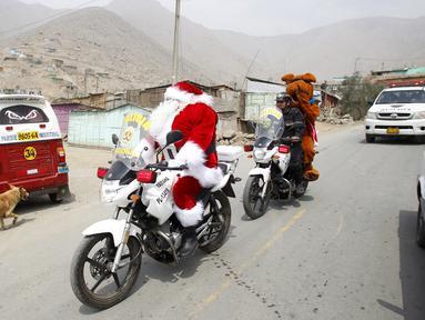 Seorang polisi Peru berpakaian seperti Santa Claus tiba dengan sepeda motornya selama perayaan Natal di Huaycan, Lima, Peru (15/12/2015). (REUTERS/Janine Costa)