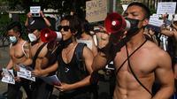 Para binaragawan berorasi saat turun ke jalan dalam protes menentang kudeta militer di Yangon, Myanmar, Kamis (11/2/2021). Memasuki hari keenam, demonstrasi menentang kudeta Myanmar dari berbagai elemen masyarakat terus berlangsung. (Sai Aung Main / AFP)