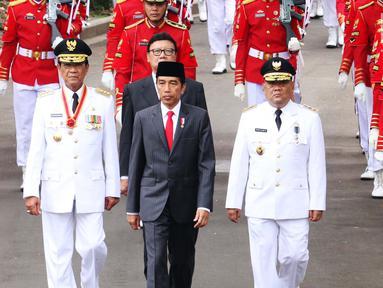 Presiden Joko Widodo (tengah), Gubernur DIY Sri Sultan Hamengku Buwono X (kiri) dan Wakil Gubernur DIY, KGPAA Paku Alam IX (kanan) kirab menuju Istana Negara, Jakarta, Selasa (10/10). (Liputan6.com/Angga Yuniar)