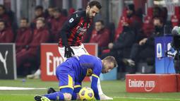Pemain AC Milan Hakan Calhanoglu (kiri) berebut bola dengan pemain Parma Simone Iacoponi pada pertandingan Serie A di Stadion San Siro, Milan, Italia, Minggu (13/12/2020). AC Milan masih puncaki klasemen usai bermain imbang 2-2 lawan Parma. (AP Photo/Luca Bruno)