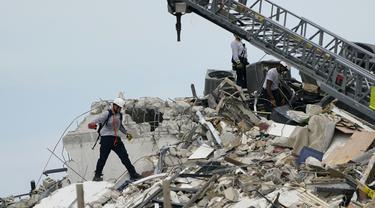 Tim penyelamat berjalan di antara puing-puing dari sebagian menara apartemen tepi laut yang runtuh di Surfside, utara Miami, Kamis (24/6/2021). Runtuhnya gedung apartemen setinggi 12 lantai tersebut mengakibatkan satu orang tewas dan puluhan lainnya masih dinyatakan hilang. (AP Photo/Lynne Sladky)