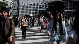 Pejalan kaki berjalan melintasi persimpangan Shibuya di Tokyo, Jepang (23/5/2019). Kota Shibuya memiliki Luas wilayah adalah 15.11 km².(AFP Photo/Behrouz Mehri)