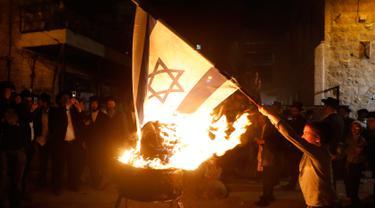 Seorang bocah Yahudi ultra ortodoks antizionis membakar bendera Israel di Yerusalem ultra-Ortodoks Mea Shearim, Rabu (2/5). Hal itu dilakukan selama perayaan Hari Raya Yahudi Lag BaOmer. (MENAHEM KAHANA / AFP)