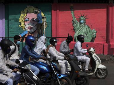 Seorang seniman melukis mural Marilyn Monroe, di samping salah satu Patung Liberty yang memakai masker untuk menyebarkan kesadaran akan pencegahan virus corona di Mumbai, India (26/3/2021). India telah melaporkan jumlah kasus virus corona tertinggi dalam empat bulan. (AP Photo/Rajanish Kakade)