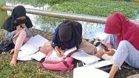 Para pelajar di Kecamatan Kinal, Kabupaten Kaur, Bengkulu harus belajar di tepi sungai karena sulitnya sinyal di desa mereka (Foto: Tomi Defantri).