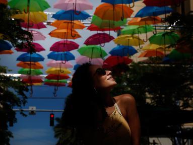 Julia Pena (19) dari Miami menikmati instalasi seni yang bernama Umbrella Sky di Coral Gables, Florida, 16 Juli 2018. Coral Gables merupakan kota ketiga di AS yang menjadi tuan rumah bagi instalasi seni yang berlangsung hingga Agustus. (AP/Brynn Anderson)