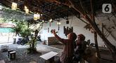 Pengunjung berswafoto di Kedai Poci (KEPO), Hj Kelik, Kelapa Dua Srengseng, Jakarta Barat, Sabtu (18/9/2021). Pemilik usaha kafe ini keluhkan sepi dikarenakan baru bisa membuka usahanya belum lama ini. (Liputan6.com/Johan Tallo)
