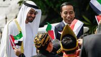 Presiden Jokowi bersama Putra Mahkota Abu Dhabi, Sheikh Mohamed Bin Zayed Al Nahyan menyapa sejumlah anak berpakaian daerah saat kunjungan kenegaraan di Istana Bogor, Kamis (24/7/2019). Keduanya menggelar pertemuan bilateral guna membahas sejumlah kerja sama. (Willy Kurniawan/Pool Photo via AP)