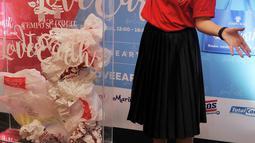 Sigi Wimala membuang sampah plastik saat acara Tempo Scan Love Earth, Jakarta, Kamis (28/4). Melalui Program Tempo Scan Love Earth, konsumen didorong untuk menggunakan tas ramah lingkungan. (Liputan6.com/Gempur M Surya)