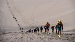 Peserta bersaing pada tahap kedua Half Marathon des Sables di Gurun Ica, Paracas, Peru, Selasa (3/12/2019). Para peserta harus menyelesaikan rute sejauh 109 Km. (Martin BUREAU/AFP)