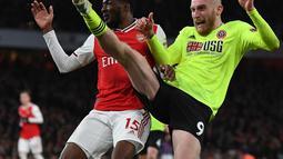 Pemain Sheffield United Oliver McBurnie (kanan) berebut bola dengan pemain Arsenal Ainsley Maitland-Niles pada pertandingan Liga Inggris di Emirates Stadium, London, Inggris, Sabtu (18/1/2020). Pertandingan berakhir 1-1. (Daniel LEAL-OLIVAS/AFP)