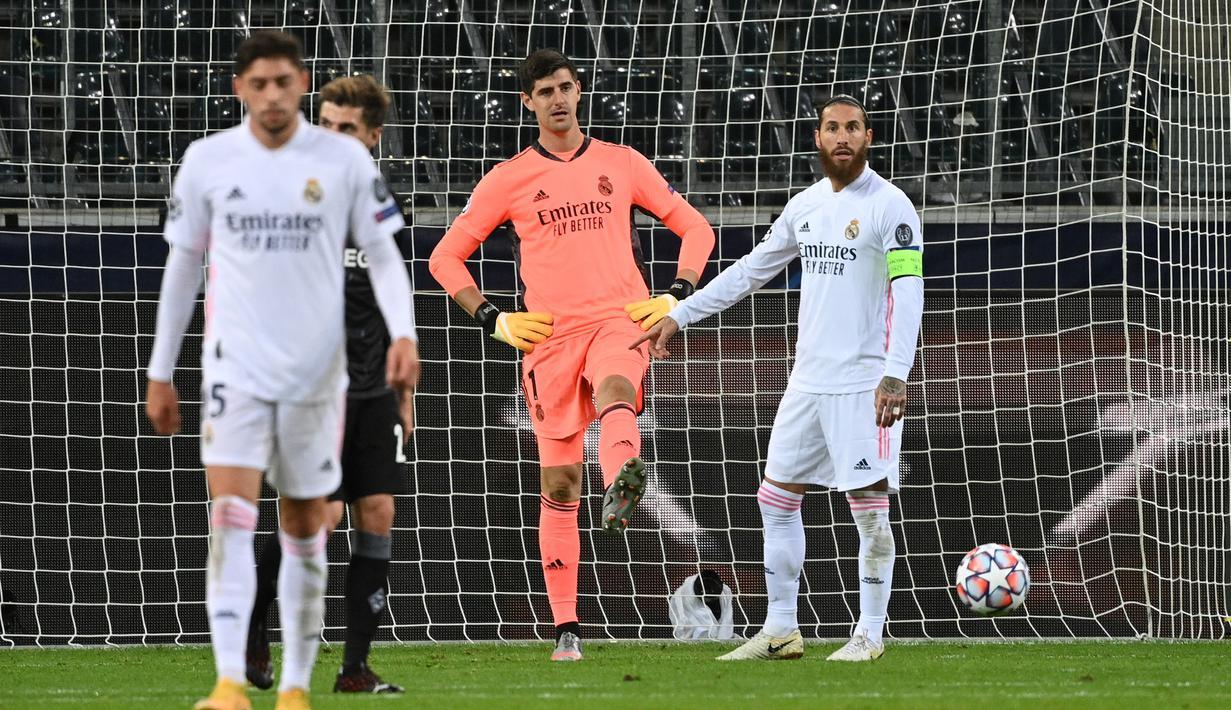 Kiper Real Madrid, Thibaut Courtois, tampak kecewa usai gawangnya kebobolan oleh Borussia Monchengladbach pada laga lanjutan Liga Champions di Borussia Park, Rabu (28/10/2020) dini hari WIB. Real Madrid bermain imbang 2-2 lawan Borussia Monchengladbach. (AFP/Ina Fassbender)