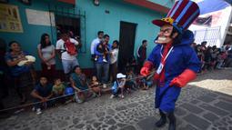 Anggota Saturno Club dengan kostum Dick Dastardly melakukan parade Dance of Costumes tahunan di sepanjang jalan kota Sumpango, Guatemala, Senin (30/12/2019). Parade kostum yang menampilkan karakter televisi dan film ini untuk memeriahkan malam pergantian tahun. (ORLANDO ESTRADA/AFP)