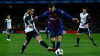Pemain Barcelona, Lionel Messi berebut bola dengan pemain Valencia, Francis Coquelin pada semifinal pertama Copa del Rey di Stadion Camp Nou, Jumat (2/2). Barcelona menang 1-0 berkat gol semata wayang Luis Suarez. (AP/Manu Fernandez)