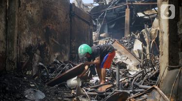 Warga mengais puing sisa kebakaran toko dan pemukiman di kawasan Manggarai, Jakarta, Selasa (7/7/2020). Tidak ada korban jiwa dalam peristiwa itu, namun akibat kebakaran sebanyak 40 bangunan yang didominasi toko mebel ludes terbakar. (Liputan6.com/Immanuel Antonius)