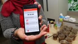 Model menunjukkan total pembayaran pada aplikasi  berbasis mobile yang menawarkan inovasi konsep restoran digital pertama di Indonesia saat Soft Launching Aplikasi MeeberLite dan Meeberian di Jakarta, Selasa (31/7). (Liputan6.com)