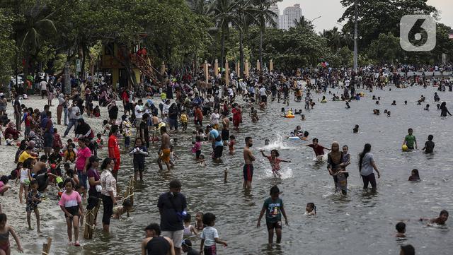 Pengunjung berenang di Pantai Karnaval Ancol, Jakarta, Jumat (14/5/2021). Pemprov DKI Jakarta pada libur Lebaran 2021 membuka sejumlah tempat wisata, salah satunya Ancol. (Liputan6.com/Johan Tallo)