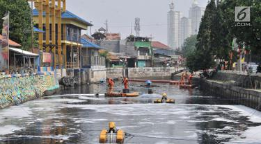 Petugas PPSU membersihkan sampah saat pengoperasian Nano Bubble dan Aerator di Kali Sentiong atau Kali Item, Jakarta, Kamis (2/8). Pemprov DKI Jakarta terus berupaya membersihkan dan mengurangi bau tak sedap di Kali Item. (Merdeka.com/Iqbal S. Nugroho)