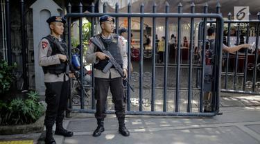 Polisi bersenjata lengkap berjaga di Gereja Katedral, Jakarta, Jumat (30/3). Penjagaan dilakukan untuk mengamankan misa Jumat Agung serta memberi kenyamanan kepada jemaat saat beribadah. (Liputan6.com/Faizal Fanani)