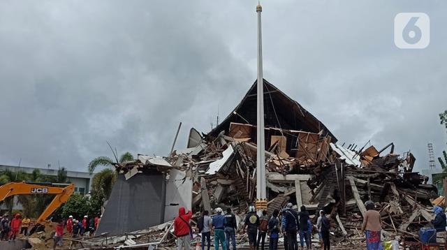 Warga melihat Kantor Gubernur Sulawesi Barat pasca Gempa Bumi dengan Magnitudo 6,2 mengguncang Majene pada Jumat 15 Januari 2021. Banyak warga yang memilih bertahan di luar rumah. Karena masih takut gempa susulan. (Liputan6.com/Abdul Rajab Umar)