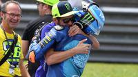 Valentino Rossi peluk sang adik, Luca Marini pada lomba Moto2 musim lalu. (Mohd RASFAN / AFP)