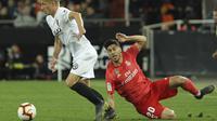 Gelandang Real Madrid, Marco Asensio, terjatuh saat berebut bola dengan pemain Valencia, Daniel Wass, pada laga La Liga 2019 di Stadion Mestalla, Rabu (3/4). Valencia menang 2-1 atas Real Madrid. (AP/Alberto Saiz)