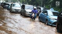 Pengendara motor melintas di antara mobil yang terjebak kemacetan saat banjir di Jalan Lapangan Banteng Utara, Jakarta, Kamis (15/2). Hujan deras yang mengguyur dan buruknya drainase menyebabkan kawasan tersebut banjir (Liputan6.com/Immanuel Antonius)