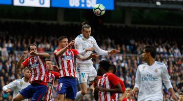 Pemain depan Real Madrid Gareth Bale berebut bola dengan pemain Atletico Madrid saat pertandingan La Liga Spanyol di stadion Santiago Bernabeu di Madrid (8/4). Real Madrid harus puas ditahan imbang 1-1 oleh Atletico Madrid. (AP Photo / Francisco Seco)