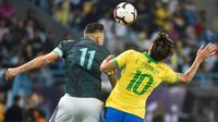 Striker Argentina Lautaro Martinez berjibaku dengan gelandang Brasil Lucas Paqueta pada uji coba di King Saud University Stadium, Jumat (15/11/2019) atau Sabtu dini hari WIB. (AFP/Fayez Nureldine )