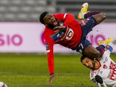 Striker Lille, Jonathan Bamba (atas) terjatuh ditekel gelandang Brest, Paul Lasne dalam laga lanjutan Liga Prancis 2020/21 pekan ke-25 di The Stade Pierre Mauroy, Lille, Minggu (14/2/2021). Lille bermain imbang 0-0 dengan Brest. (AP/Michel Spingler)