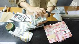 Teller tengah menghitung mata uang dolar AS di penukaran uang di Jakarta, Rabu (10/7/2019). Nilai tukar rupiah terhadap dolar Amerika Serikat (AS) ditutup stagnan di perdagangan pasar spot hari ini di angka Rp 14.125. (Liputan6.com/Angga Yuniar)