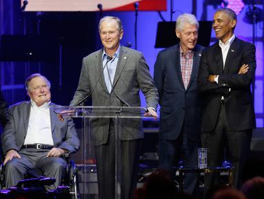 Mantan Presiden George W. Bush (tengah) didampingi empat mantan Presiden AS lainnya berpidato dalam acara konser amal di College Station, Texas (21/10). (AP Photo/LM Otero)