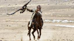 """Seorang pria Kirgistan menunggang kuda sambil memegang elang emas selama festival berburu """"Salburun"""" di Tuura-Suu, Bishkek, Kyrgyzstan, Selasa (23/2/2021). Salburun berasal dari tradisi nomaden berburu dan melindungi penggembala dari predator seperti serigala. (AP Photo/Vladimir Voronin)"""