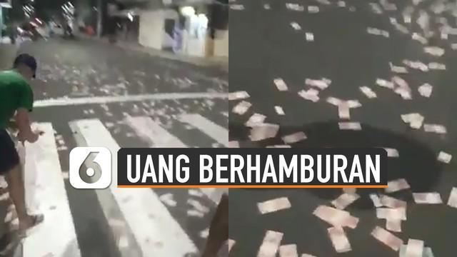 Terlihat momen ketika warga sedang memunguti uang-uang kertas yang berada di tengah jalan.