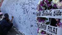 Karangan bunga diletakkan di sisi banner tulisan dukungan buat Polri pasca kerusuhan di Rutan cabang Salemba Mako Brimob saat acara Car Free Day di Kawasan Bundaran Hotel Indonesia, Jakarta, Minggu (13/5). (Liputan6.com/Helmi Fithriansyah)