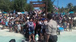 Polisi mengatur saat ratusan orang berusaha meninggalkan Gili Trawangan, NTB, Senin (6/8). Evakuasi dilakukan secara bertahap menggunakan perahu karet menuju kapal yang sudah disiapkan Basarnas. (Handout/Indonesia Water Police/AFP)